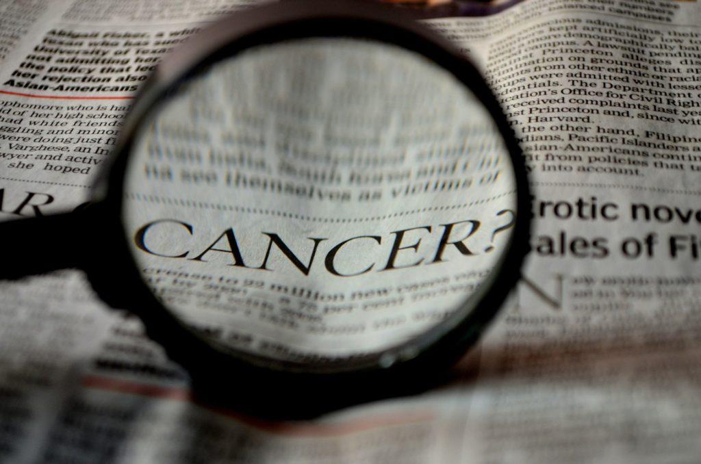 """Eine Lupe zeigt auf das Wort """"Cancer"""" (Krebs) in einem Zeitungsartikel Sterbende mit Krebs begleiten, Symptome bei Krebserkrankungen, Sterbebegleitung, Krebs im Endstadium"""